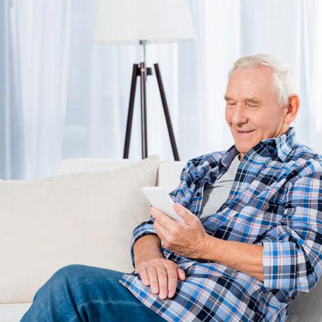 Senior mit Smartphone auf Sofa